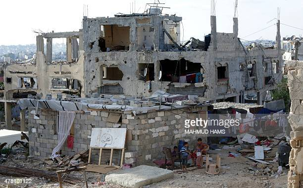 Palestinian children play next the remains of their house on June 22 2015 in Gaza City that was destroyed during 50day war between Israel and...