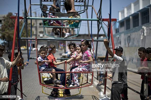 Palestinian children play on a mini ferris wheel outside an United Nations school in Jabalia in the northern Gaza strip, on July 28 on the beginning...