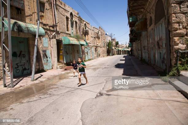 Palestinian children play on an abandoned Shuhada street in the old town of Hebron which is under Israels military control on June 14 2018 Not many...