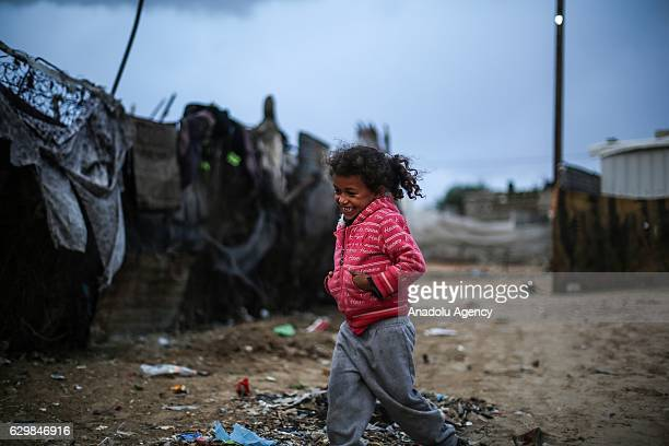 Palestinian children play outside as Palestinians living in makeshift homes in ElZohor neighborhood in the city of Khan Yunis on the Gaza Strip are...