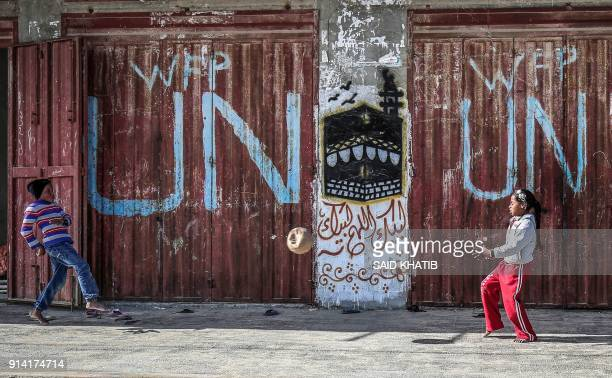 TOPSHOT Palestinian children play with a ball outside a UN food distribution warehouse at the Rafah refugee camp in the southern Gaza strip on...