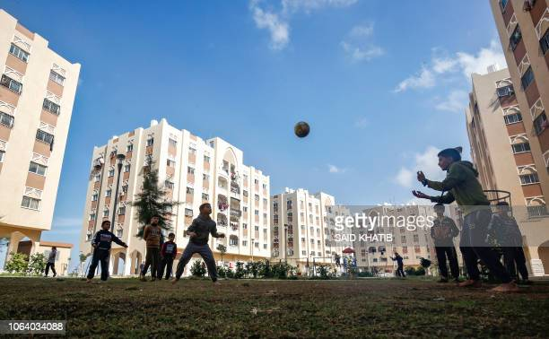 Palestinian children play with a football in a courtyard between new Qatari-built residential units in Khan Yunis in the southern Gaza Strip on...