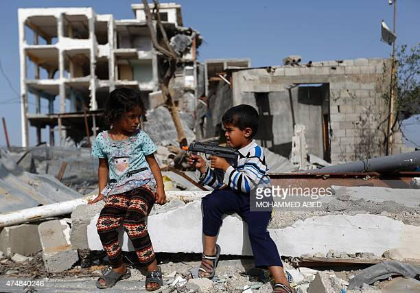 Palestinian children play with a toy gun on May 27 2015 in front of bulldings that were destroyed during the 50day war between Israel and Hamas...