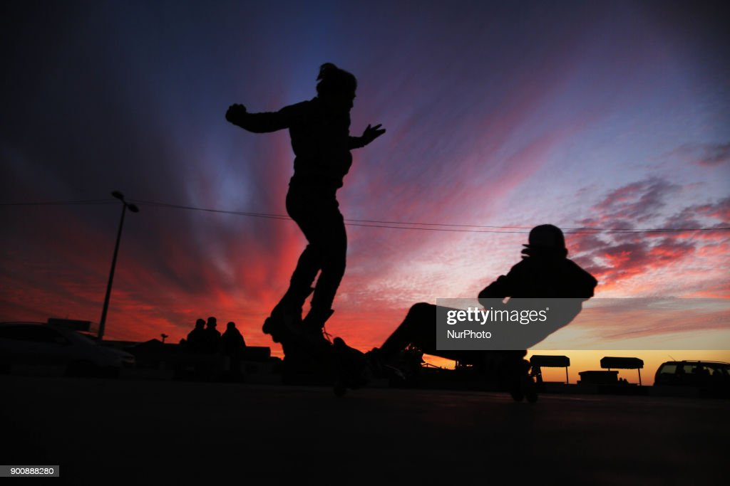 Palestinian children play with bicycles and skates in the Gaza Port at sunset 3-1-2018