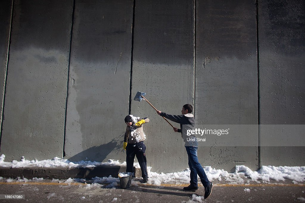 Palestinian children play with snow in front of the controversial Israeli separation barrier on January 10, 2013 in the West Bank village of Abu Dis, at outskits of Jerusalem.