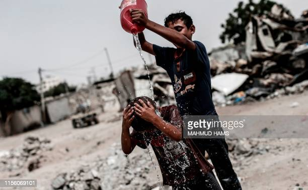 Palestinian children play with water in a slum on the outskirts of the Khan Yunis refugee camp, in the southern Gaza Strip on July 17 during a heat...