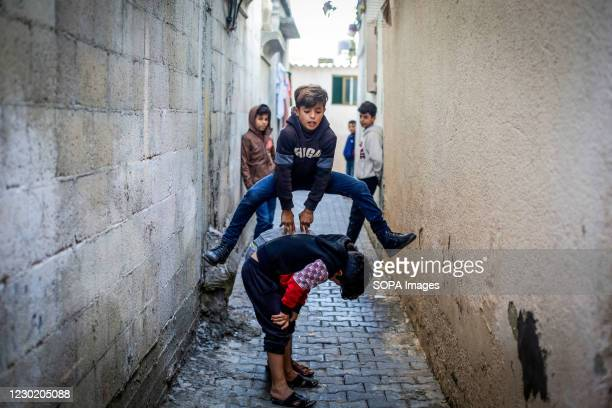 Palestinian children playing leap frog outside their home in Jabalia camp in the northern Gaza Strip.