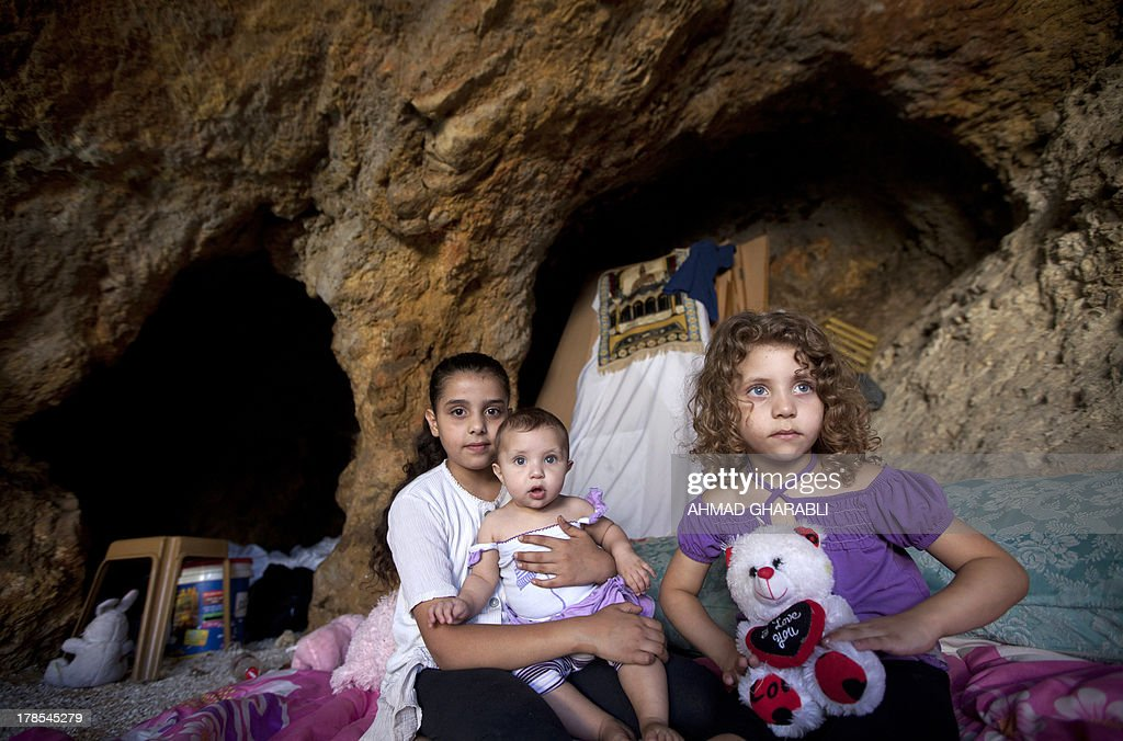DAVISON - Palestinian children pose on a makeshift bed in the cave that hosts their family since the demolition of their house by Israeli forces on August 29, 2013 in the east Jerusalem neighborhood of Silwan. Israeli forces have destroyed the homes of 716 Palestinians in 2013, according to HRW, which has recorded a three-fold increase in the number of demolitions in east Jerusalem since last year.