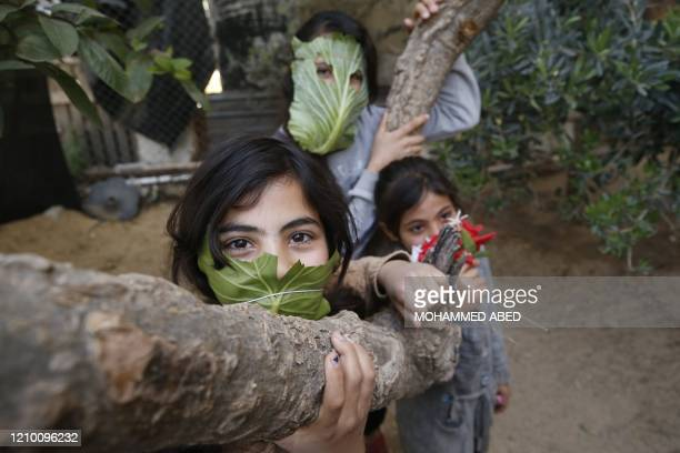 Palestinian children pose with makeshifts masks made of cabbage while cooking at home with their family in Beit Lahia in the northern Gaza Strip on...