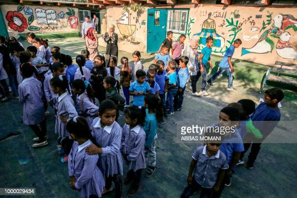 Palestinian children queue up before the early start of classes at a school in the Bedouin village of Khan alAhmar in the occupied West Bank during...