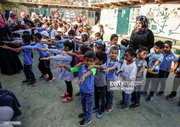 Palestinian children queue up before the early start of classes at a school in the Bedouin village of Khan alAhmar in the occupied West Bank on July...