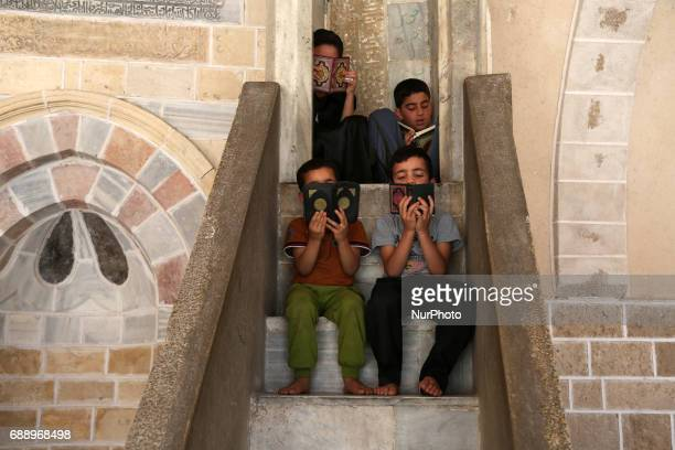 Palestinian children read copies of the Koran Islam's holiest book on the first day of fasting in the Muslim holy month of Ramadan at the alOmari...