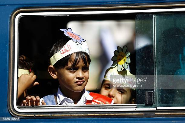 Palestinian children ride a bus as they take part in a festival marking the World Mental Health Day on October 11 2016 in Gaza City / AFP / MOHAMMED...