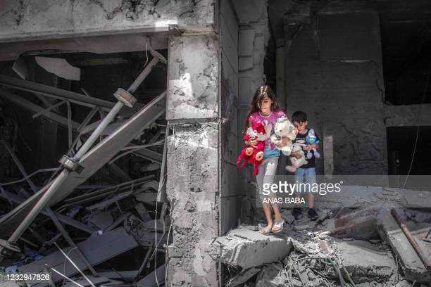 Palestinian children salvage toys from their home at the Al-Jawhara Tower in Gaza City's Rimal neighbourhood, on May 17 which was heavily damaged in...