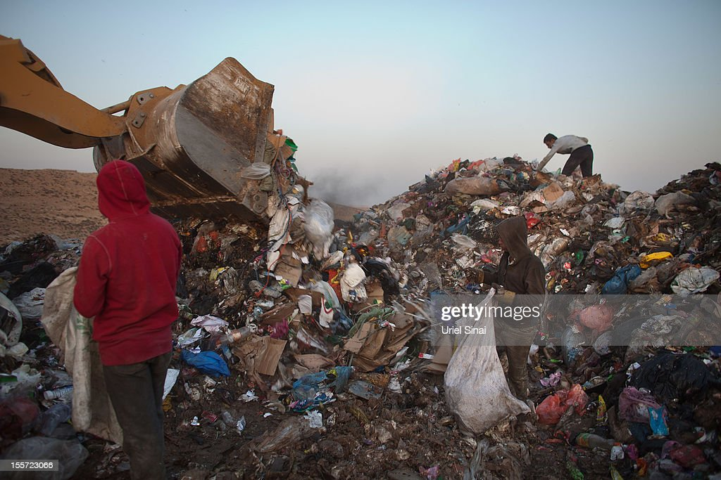 Palestinian children sift through a garbage dump on November 7, 2012 south of Hebron, West Bank. About 40 Palestinain men and children work at the West Bank garbage dump looking for clothing, metal and wood discarded, in large part, from the Jewish settelment in the region.