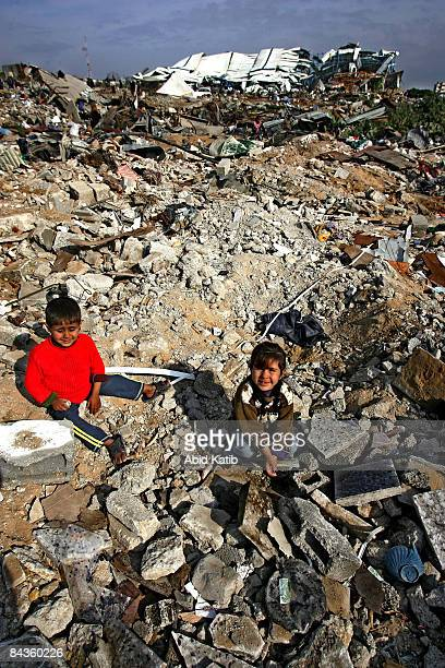 Palestinian children sit amongst the rubble of their family home destroyed by an Israeli airstrike on January 19, 2009 in Jabalia, Gaza Strip. While...
