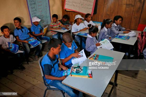 Palestinian children sit in a classroom after the early start of classes at a school in the Bedouin village of Khan alAhmar in the occupied West Bank...