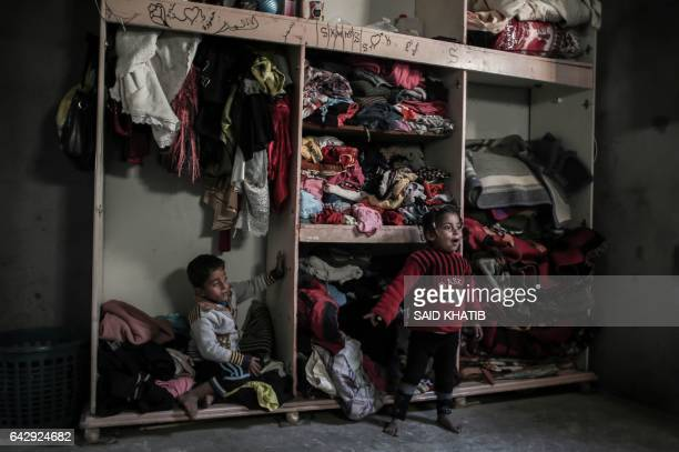 Palestinian children sit inside their house in an impoverished area in the southern Gaza Strip town of Khan Yunis on February 19, 2017. / AFP / SAID...