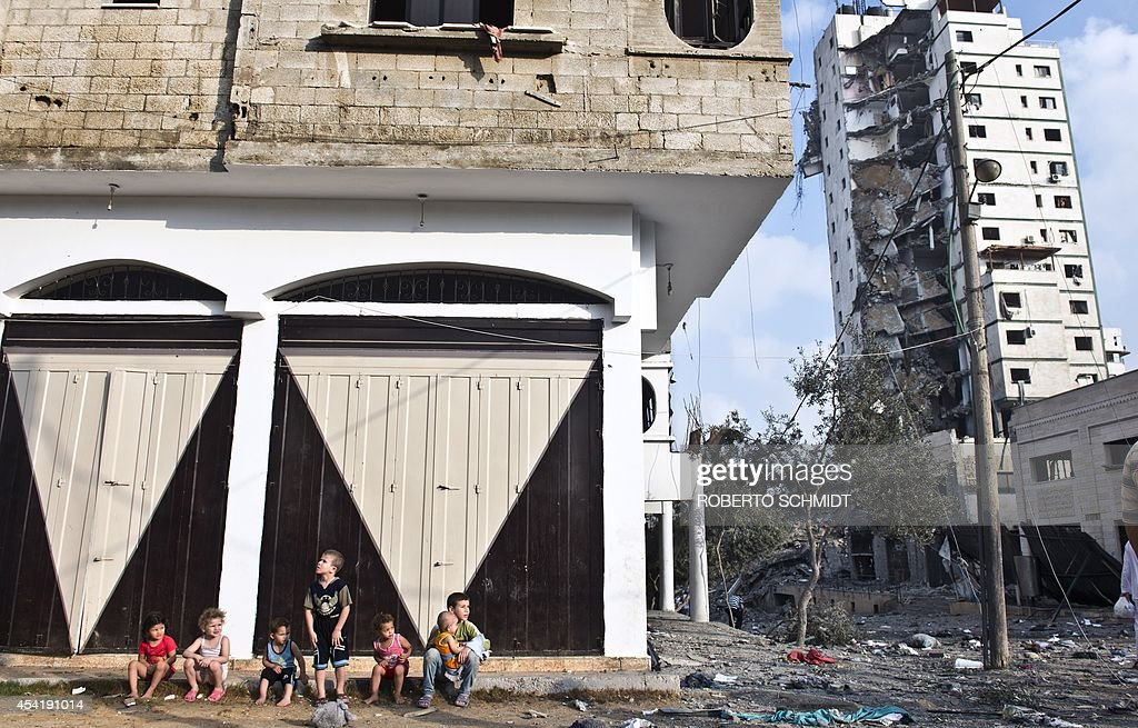 Palestinian children sit on a sidewalk as they wait for their parents to retrieve some of their family's belongings from a partially destroyed house across the street from a high rise apartment building in Gaza City (R) that was targeted by Israeli airstrikes overnight on August 26, 2014. The UN estimates that about a quarter of the 1.8 million inhabitants of Gaza have been displaced by fighting between Hamas militants and Israel since fighting started on July 8.