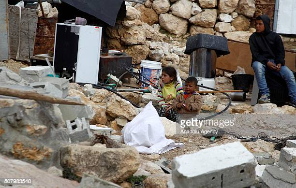 Palestinian children sit on the debris of their house which was demolished by Israeli authorities on the ground that the house was unauthorized in...