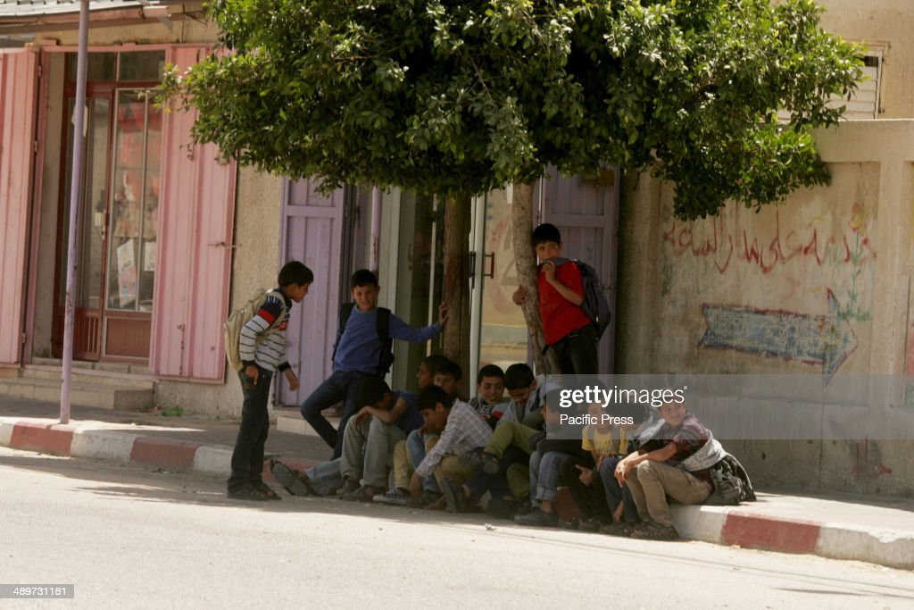 Palestinian children sit on the edge of the pavement in a... : ニュース写真