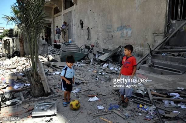 Palestinian children stand amongst the ruins of buildings destroyed in air attacks staged by Israel army to hit the al-Raziq's house within the scope...
