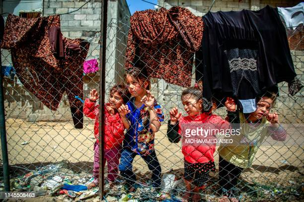 TOPSHOT Palestinian children stand behind a wire fence in an impoverished area in Beit Lahia in the northern Gaza Strip on May 22 2019