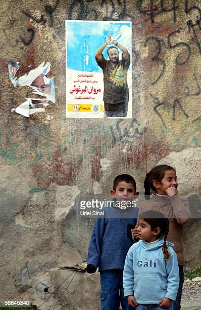 Palestinian children stand under a campaign poster for the jailed proFatah leader Marwan Barghoutti for the Palestinian parliamentary elections...