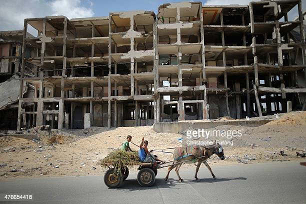 Palestinian children travel on the donkey cart past destroyed buildings that continue to scar the landscape of Gaza on June 10 Gaza City Gaza The...