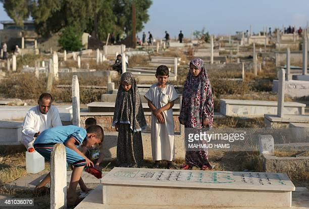 Palestinian children visit the grave of a relative at a cemetery in Gaza City's eastern suburb of AlShejaiya on July 17 in the early hours of the...