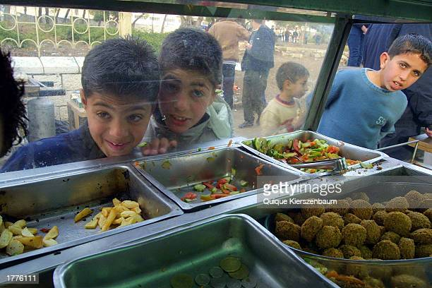 Palestinian children wait for their falafel sandwich during celebrations of the Muslim holiday of Eid alAdha in a park February 11 2003in East...