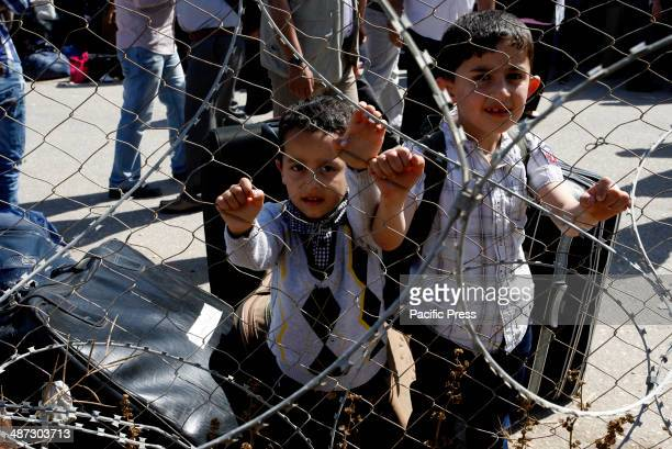Palestinian children wait with a their families at the Rafah border crossing between Egypt and the southern Gaza Strip. Egyptian authorities...