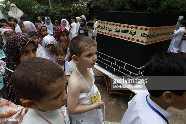 Palestinian children walk around a makeshift cube representing the holy Kaaba in Gaza City on October 22 as part of training children how to perform...