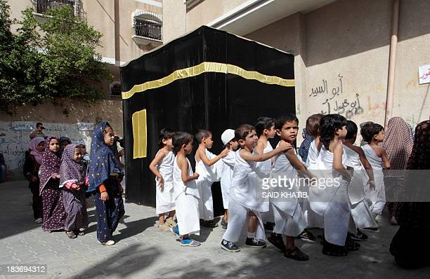 Palestinian children walk around a replica of the Kaaba stone which is found in the holy city of Mecca Saudi Arabia as youngsters learn about Islam...