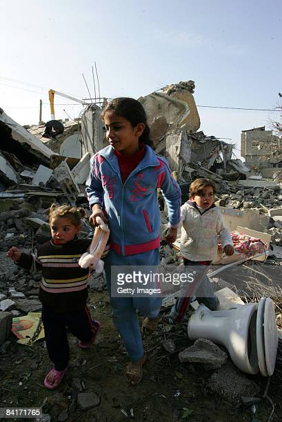 Palestinian children walk over rubble after an Israeli airstrike on January 5 2009 in Rafah southern Gaza Israel is intensifying its widescale ground...