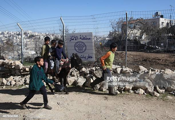 Palestinian children walk past a sign written in Arabic from the Israeli Antiquities Authority at an excavation site at Tel Rumeida in the heart of...