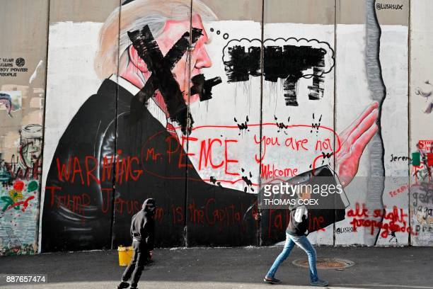 Palestinian children walk past vandalised graffiti depicting US President Donald Trump and slogans against the US Vice President painted on Israel's...