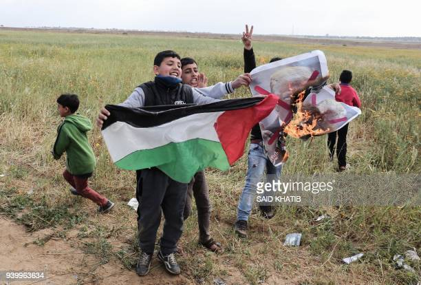 TOPSHOT Palestinian children wave a Palestinian flag as they burn a crossedout poster depicting US President Donald Trump during a tent city protest...