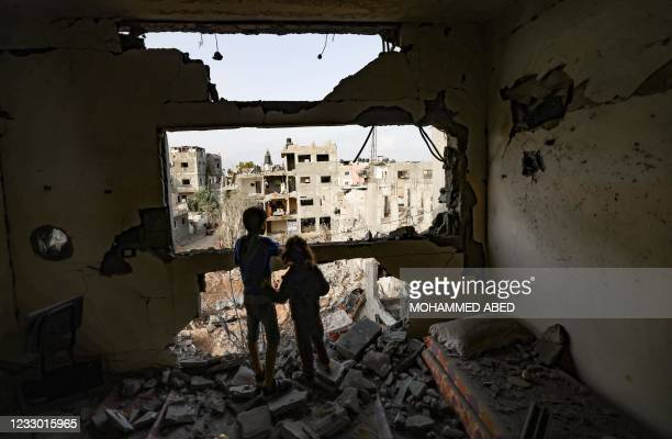 Palestinian children who have returned to their neighbourhood, stare at the damaged from their home, hit by Israeli bombardment in Gaza City, after a...