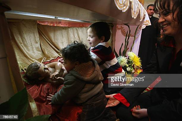 Palestinian Christian children crawls under the altar to touch the doll representing the infant Jesus after Christmas Day mass in St Catherine's...