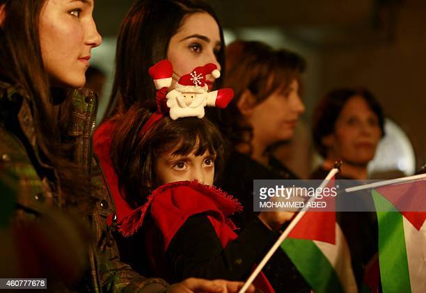 A Palestinian Christian family attend a celebration before Christmas at the orthodox church of Gaza City on December 22 2014 as Christians around the...