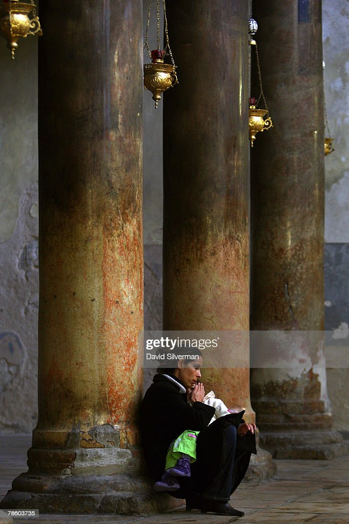 A Palestinian Christian holds her child as she sits as the base of a marble column in the Church of the Nativity, the traditional birthplace of Jesus, December 21, 2007 in Bethlehem in the West Bank. The biblical town is celebrating both Christmas and the Muslim Eid al-Adha over the next few days.