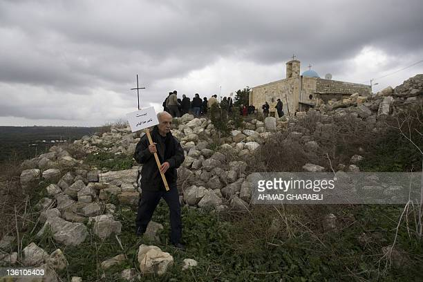 A Palestinian Christian man walks in the rubble of their native Palestinian village of Iqrit to place the name of the owner of a destroyed house...