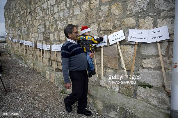 A Palestinian Christian man walks past the Arabic signs with the names of the owners of houses which were destroyed in 1948 in his native Palestinian...