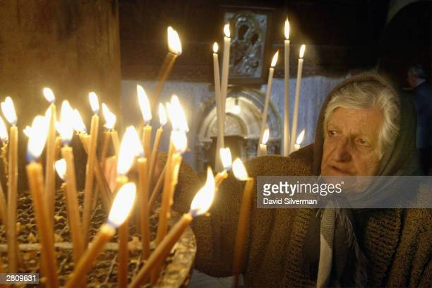 Palestinian Christian woman Anna Elias lights votive candles December 14 2003 in the Church of the Nativity in the West Bank town of Bethlehem The...