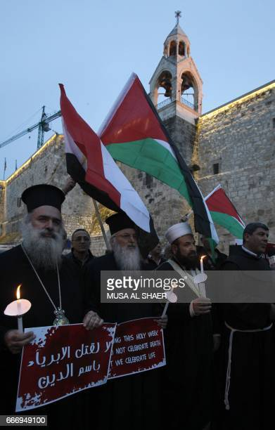 Palestinian Christians and Muslims clergymen hold candles and wave Palestinian and Egyptian national flags during a gathering in the West Bank town...