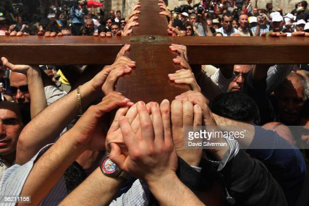 Palestinian Christians carry their large wooden cross along the Via Dolorosa, the route tradition says Jesus carried the cross on which he was to be...