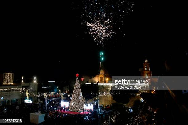 Palestinian Christians watch as fireworks light the sky to mark the lighting of a Christmas tree on December 1 2018 at the Manger Square near the...