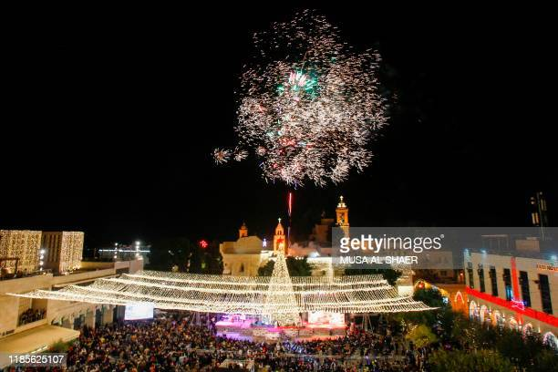 Palestinian Christians watch as fireworks light the sky to mark the lighting of a Christmas tree on November 30 2019 at the Manger Square near the...