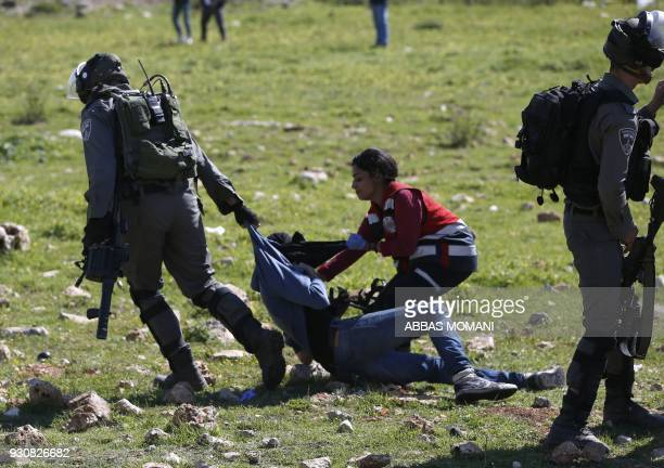 Palestinian Civil Defence volunteer tries to free a Palestinian demonstrator from the grip of an Israeli soldier on March 12 2018 in the West Bank...